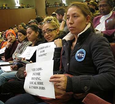 Protesters demand union wages at a December hearing on the Mayor's housing plan.
