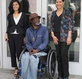 Tenant Terrance Handy outside 1434 Ogden Ave. with Bronx Legal Services lawyers Kulsoom Ijaz, left, and Cristina Castro. Photo by Steven Wishnia.