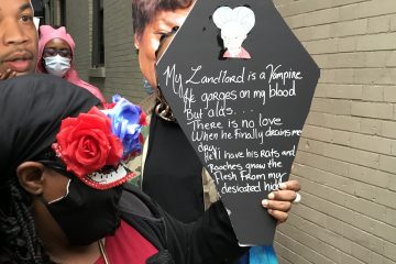 Tenant protestor holding sign in the shape of a coffin with a poem about their landlord written on it