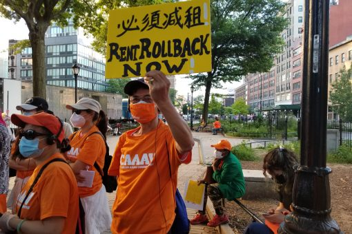 Tenants from CAAAV hold up sign in Chinese and English demanding a rent rollback